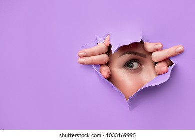 close-up of female fingers, nose and eyes that can be seen through a hole in bright purple paper