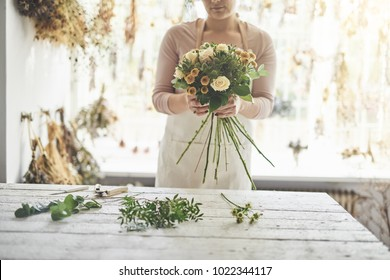 Closeup of a female florist standing at a table in her flower workshop holding a bouquet of roses and mixed flowers
