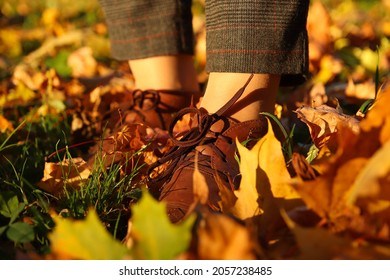 Close-up female foot in capri pants and brogues shoes on dry autumn bright leaves background. Bright stylish woman in orange coat walking in october park.