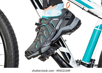 Closeup of the female foot in special contact shoe attached to the bicycle pedal.