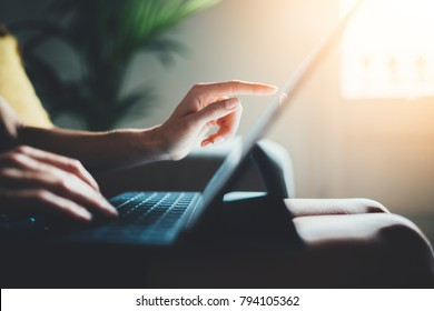 Closeup of female freelancer businesswoman working from home via modern portable computer device, young hipster girl using digital tablet while working at loft studio, flare light on the background