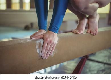 Close-up of female gymnast practicing gymnastics on the balance beam
