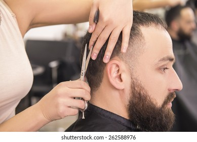 Close-up female hairdresser cutting hair of man client.