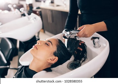 Closeup of female hairdresser rinsing hair of a customer . Woman getting hair spa at hair dressing salon.