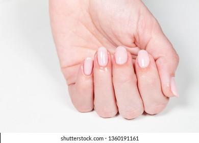 Closeup of female hand with beautiful natural fresh pink manicure with skin wet from moisturizing cuticle oil. Horizontal color photography.