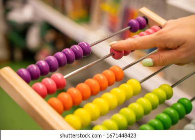 Closeup female hand calculating with balls on wooden rainbow abacus for number calculation. The concept of learning arithmetic for preschoolers.