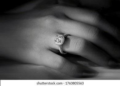 Closeup of female hand with  diamond engagement ring  black and white