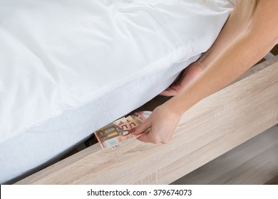 Close-up Of A Female Hand Hiding Banknotes Under Bed