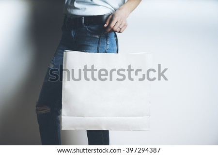 Close-up of female hand holding blank white paper package on white background, mock-up of white shopping bag with handles