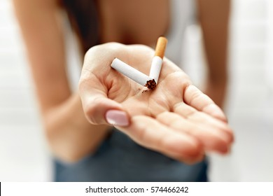 Closeup Of Female Hand Holding Broken Cigarette On Palm. Close-up Of Woman's Hand With Cigarette On It. Quit Smoking Cigarettes Concept. High Resolution