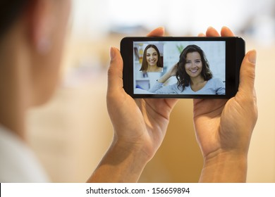 Closeup of a female hand holding a cell phone during a skype video call with her friend