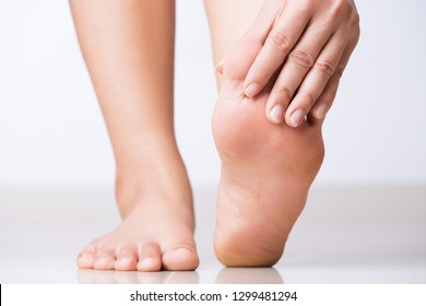 Closeup female hand holding foot pain, Healthcare concept.