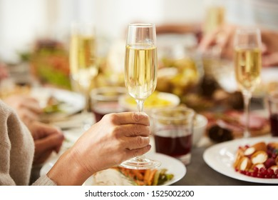 Close-up of female hand holding glass with champagne while have dinner at the table