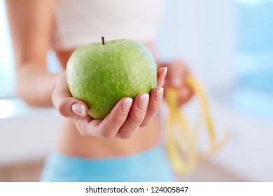 Close-up of female hand holding green apple