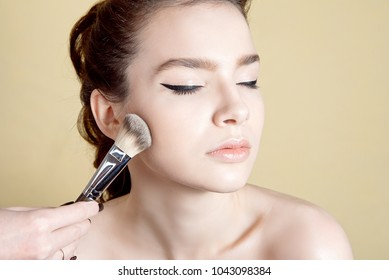 Close-up female hand holding makeup brush near model face.
