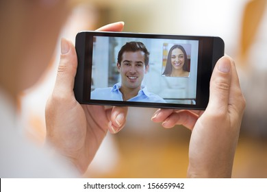 Closeup of a female hand holding a smart phone during a skype video call with her friend