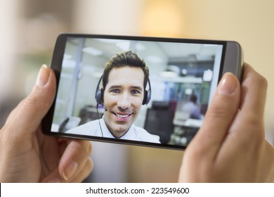 Closeup of a female hand holding a smart phone during a skype video