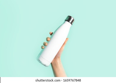 Close-up of female hand, holding white reusable steel stainless eco thermo water bottle with mockup, isolated on background of cyan, aqua menthe color. Be plastic free. Zero waste.