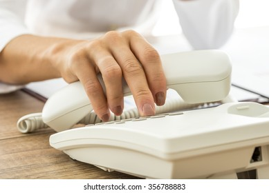 Closeup of female hand holding a white landline telephone handset and dialing a phone number at the same time.