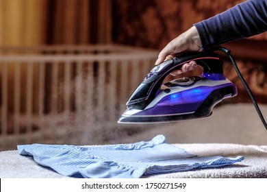 Closeup female hand ironing clothes on the table. Puffs of hot steam break out of the iron. Dark blurred background.