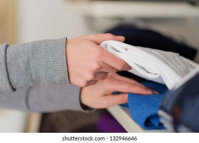 Close-up Of Female Hand Picking Shirt, Indoors