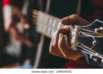 Close-up of female hand playing guitar