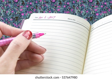 Closeup of female hand ready to write on personal agenda in new year January 1 2017, floral background