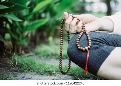 Close-up of female hand sitting, holding rosary beads and meditating outdoors