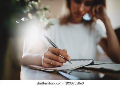 Closeup of female hand writing in notebook, pensive student girl learning at home, businesswoman working in modern loft, young hipster girl freelancer working in comfortable coffee shop