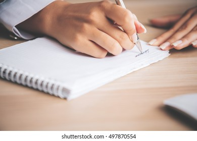 Closeup of female hand writing in spiral notepad placed on light wooden desktop