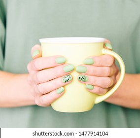 Close-up of female hands with art leaf nails design and trendy summer stylish green manicure holding a cup.