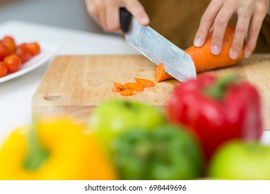 Close-up of female hands cutting carrot on board