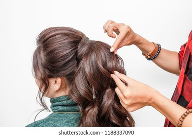 Closeup of female hands of hairdresser or coiffeur makes hairstyle. Event hair fashion and business concept