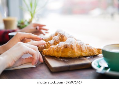 Closeup of female hands having croissants in coffee shop