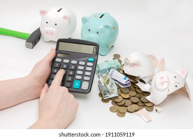 closeup female hands hold a calculator, money is counted. A broken piggy bank with money lies nearby. Two complete piggy banks will be broken later. Horizontal photo