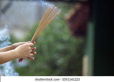 A closeup of female hands holding a bunch of smoking incense sticks. Blurry temple in the background. Copy space.