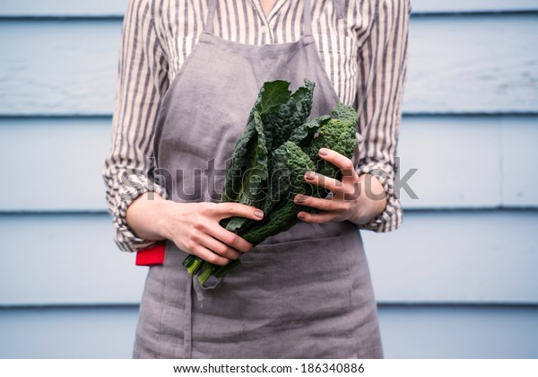 Closeup of Female Hands Holding Bunch of Green Italian Kale