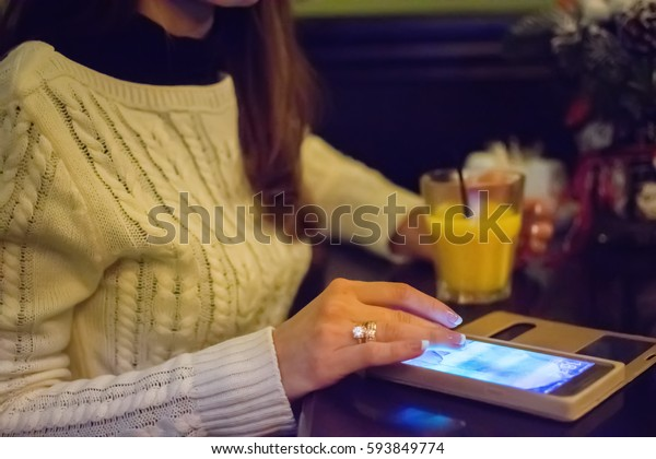 close-up of female hands holding a cell phone, sitting at the bar, next to a fruit juice