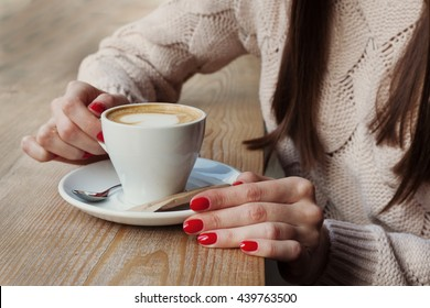 Close-up female hands holding cup with coffee cappuccino with foam with pattern heart. Perfect red gel polish manicure. Wood natural table. Creative color warm post processing instagram style.