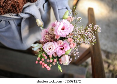 Closeup of female hands holding fresh bouquet of beautiful flowers
