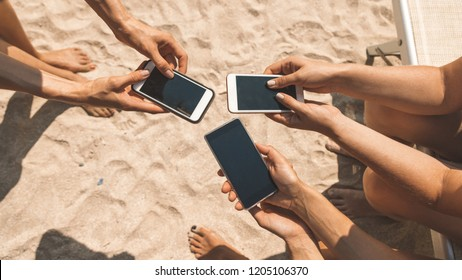 Close-up of female hands holding phones chatting on social network or shopping online on the beach. Compulsive smartphone and internet use (addiction) of young people (millennials) concept