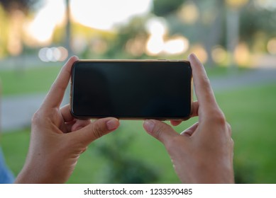 Closeup of female hands holding smart phone on outdoors background. Top side overhead view of mockup display nature backdrop, modern digital device mobil communication technology connection