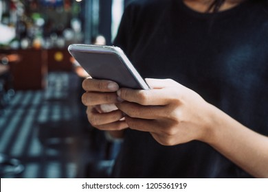 Close-up of female hands holding smartphone and texting message, networking or using application. Mobile technology concept