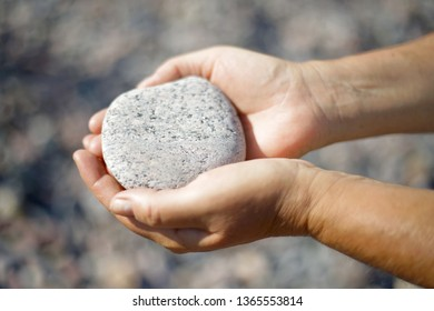 Closeup of female hands holding a stone in warm evening light