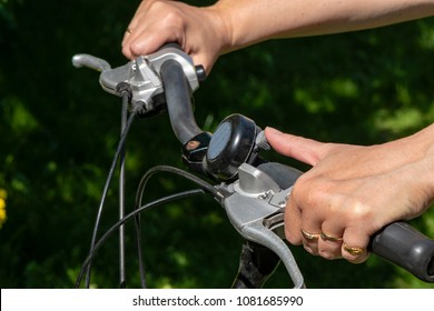Close-up of female hands on a bicycle handlebar while ringing