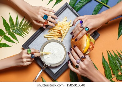 Close-up of female hands in original jewelry, rings. The girl eats exquisite dishes in a plate on a colored background. Top view.