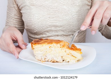 Close-up of female hands and a piece of meat pie