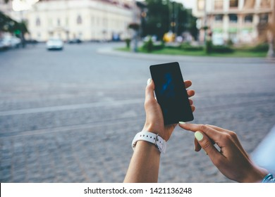 Close-up female hands pointing device screen on the background of old city street. Young woman using smart phone standing near european paving stone road with cars.