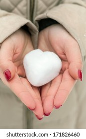 close-up of female hands with snow heart