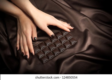 Closeup of female hands touching the dark chocolate bar